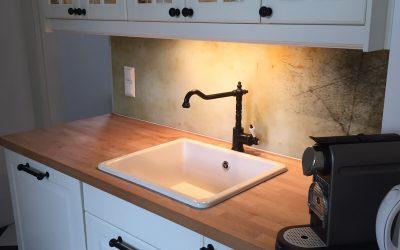Die bedruckte Glasplatte im rostigen Design passt farblich zur hellen Küchenarbeitsplatte